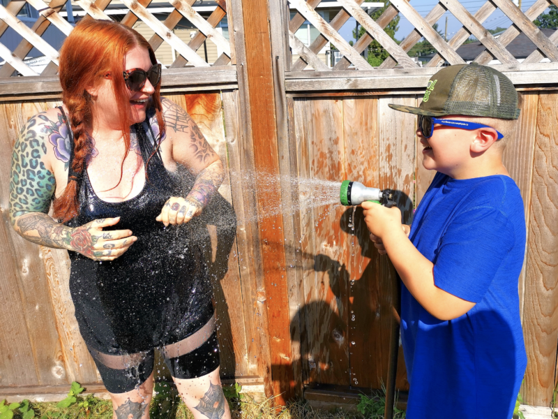 A photo of a woman being sprayed with a hose by a child.