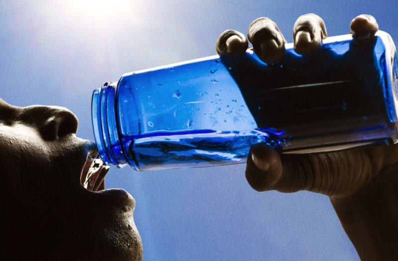 Adult male drinking water after working out.