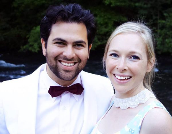 A photo of a man, Seth Ginsberg, wearing a white tuxedo and a woman, Cara Zelas wearing a printed dress.
