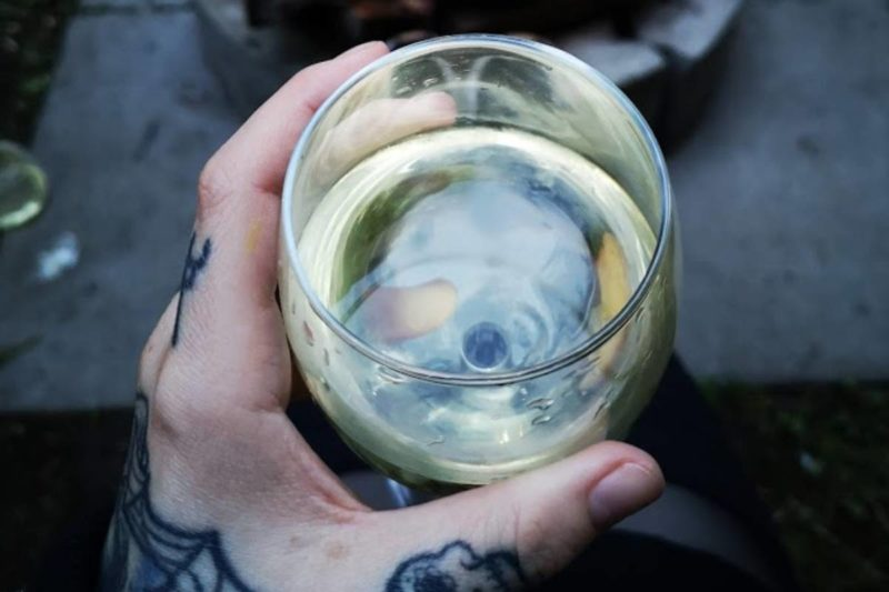 A photo of a hand holding a glass of white wine.
