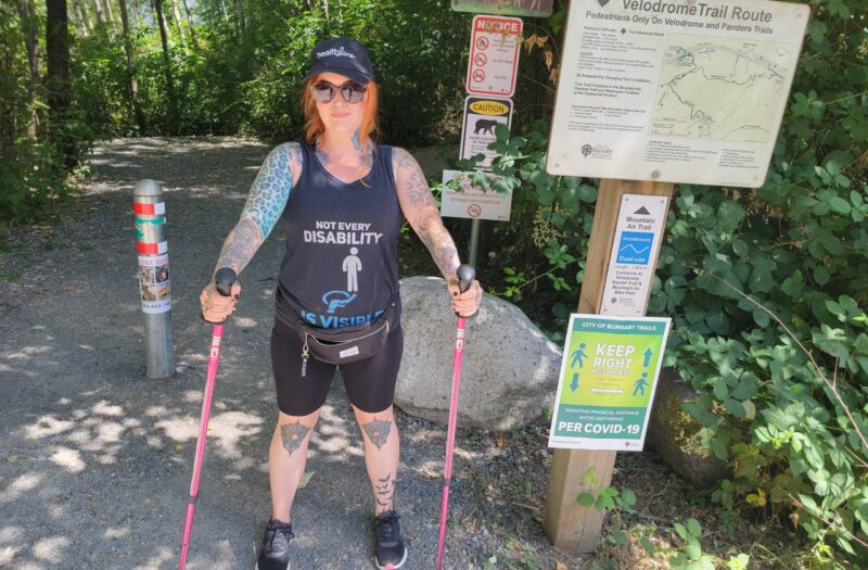 A photo of a woman, Eileen Davidson, standing in front of the entrance to a hike. She is holding hiking poles.