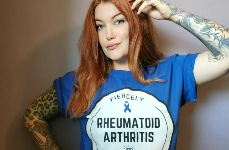 """A photo of a woman, Eileen Davidson, modeling the """"Fiercely Fighting Rheumatoid Arthritis"""" t-shirts, which will be available for purchase following the Tumbler and Tipsy by Michael Kuluva 2022 Collection event, airing on Tuesday, September 14, 20201 at 8 p.m. ET via YouTube. Eileen is wearing a blue shirt with a white circle outlined in black. Within the white circle are the words """"Fiercely."""" Beneath that is a blue ribbon to symbolize arthritis awareness. Below the ribbon are the words """"Rheumatoid Arthritis."""" Below those words are an image of a hand in a fist with lightning bolts. Below the hand is the worth """"Fighting."""
